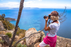 Nature photographer. Nature travel photographer woman taking pictures on a spectacular cliff during the trek Fluted Cape Within the South Bruny National Park Royalty Free Stock Image