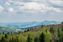 Nature of Ukrainian mountains in spring. Green hills of the Carpathian Mountains in Ukraine. Natural landscape with awaking colors of forest. Cloudy sky and stock images