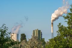 Nature under the influence of nearby power plant with heavily smoky chimney royalty free stock images