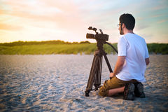 Nature Videography. A videographer documanting a sunset on the beach Stock Photos