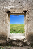 Nature view behind window. Green grass and blue sky behind old castle window Royalty Free Stock Photos