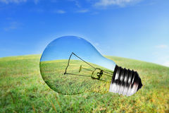 Nature view in light bulb. Green grass and blue sky view in light bulb Royalty Free Stock Image