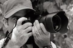 Nature and Wildlife Photographer. Looks through a camera outdoor Stock Photos