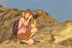 Nature woman photographer. With camera takes picture outdoor. Caucasian female with backpack shooting on mountain top.Professional photographer takes photo of Royalty Free Stock Image