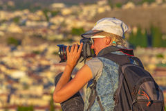 Nature woman photographer. With camera takes picture outdoor. Profile of caucasian female with backpack shooting during a trekking.Professional photographer Royalty Free Stock Photography