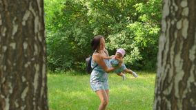 A woman turns a baby in her arms. In nature, a woman turns a baby in her arms and smiling, laugh stock video footage