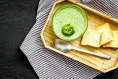 Naturel, aliment biologique Soupe-purée végétale verte dans tout préparé de cuvette servie avec des biscottes sur la copie noire  photographie stock