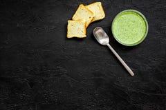 Naturel, aliment biologique Soupe-purée végétale verte dans tout préparé de cuvette servie avec des biscottes sur la copie noire  Image libre de droits