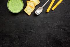 Naturel, aliment biologique Soupe-purée végétale verte dans tout préparé de cuvette servie avec des biscottes sur la copie noire  Photo stock