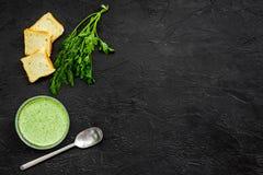 Naturel, aliment biologique Soupe-purée végétale verte dans tout préparé de cuvette servie avec des biscottes sur la copie noire  Photos libres de droits