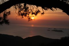 Naturel framed Sunset. Sunset over sea with little islands framed by pine tree and mountains Royalty Free Stock Images