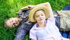 Naturen fyller dem med lugn och fred Den orakade mannen och flickan lägger på gräsäng Drömlikt sömnigt för grabb och för flicka arkivfoton