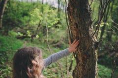 A natureza de exploração da menina da criança na floresta adiantada da mola caçoa a aprendizagem amar a natureza Crianças de ensi foto de stock royalty free