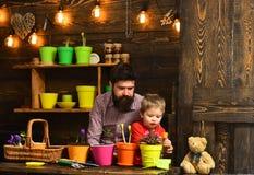 Natureza farpada do amor da crian?a do homem e do rapaz pequeno Molhar do cuidado da flor Adubos do solo jardineiro felizes com f imagens de stock
