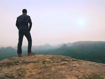 Naturfotvandrare på den skarpa klipparocen som håller ögonen på över den dimmiga dalen till den suddiga horisonten Ruskig regnig  Royaltyfri Fotografi