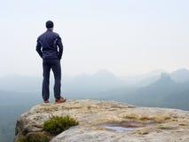 Naturfotvandrare på den skarpa klipparocen som håller ögonen på över den dimmiga dalen till den suddiga horisonten Ruskig regnig  Fotografering för Bildbyråer