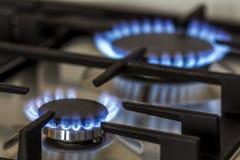 Naturgasbränning på kökgasugnen i mörkret Panelen från stål med en gascirkelgasbrännare på en svart bakgrund, närbild shoo royaltyfri fotografi
