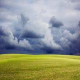 Naturhintergrund mit grüner Wiese, stürmischem Himmel und Regen Lizenzfreie Stockfotografie
