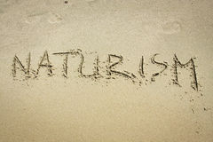 Naturism. 'Naturism' - handwritten in sand beach Stock Images