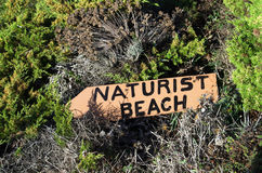 Naturist beach sign. Lost in the middle of the vegetation stock image
