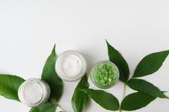 Naturkosmetikcreme, Seesalz mit Blättern für weißen Tabellenhintergrund des selbst gemachten Badbadekurortes für Draufsichtspott  stockbild
