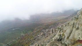 Naturlandschaft, Ansicht von der Spitze des Hügels auf gelbem und grünem Tal im starken Nebel schuß Antenne für steile Steigung v stock video footage