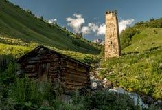Naturlandschaft von Landschaft Kaukasus Svaneti mit altem mittelalterlichem Verteidigungssteinturm, der Gebirgszug, Gletscherbach Stockbild