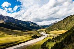 Naturlandskap av att bedöva berg och vatten under klar blå himmel med moln arkivbild