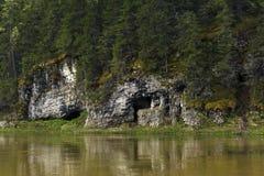 Naturlig grotta i en flodbank royaltyfria foton