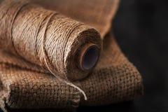 Naturlig jute tvinnar rulle, säckväv på svart bakgrund Tillförsel och hjälpmedel för handgjord hobbyfritid Royaltyfri Fotografi