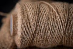 Naturlig jute tvinnar rulle, säckväv på svart bakgrund Tillförsel och hjälpmedel för handgjord hobbyfritid Arkivfoto