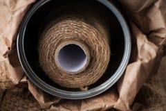 Naturlig jute tvinnar rulle, säckväv på svart bakgrund Tillförsel och hjälpmedel för handgjord hobbyfritid Arkivbild