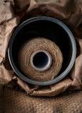 Naturlig jute tvinnar rulle, säckväv på svart bakgrund Tillförsel och hjälpmedel för handgjord hobbyfritid Royaltyfri Bild