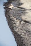 Naturlig kust med stenar och insnöad vinter arkivfoton