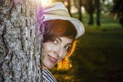 Naturlig kvinna som poserar med trädet i soligt panelljus arkivbilder