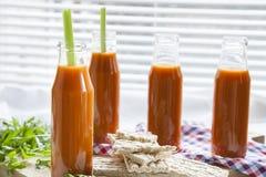 Naturlig och ny morotfruktsaft i små flaskor med ny selleri och vanlig råg bakar ihop arkivbilder