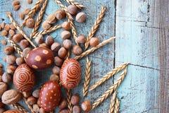 Naturlig ordning för påskägg med hasselnötter som stavas, aprikoskärnor valnötter Arkivbild