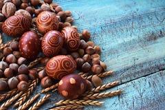 Naturlig ordning för påskägg med hasselnötter som stavas, aprikoskärnor valnötter Arkivfoto