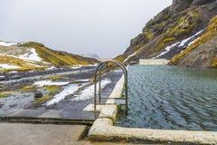 Naturlig simbassäng Seljavallalaug i Island med mannen i vatten och snöig väder och berg lite varstans Royaltyfri Fotografi