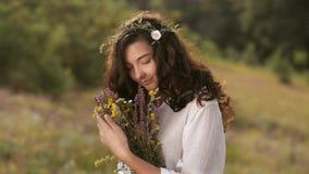Naturlig skönhetflicka med buketten av blommor som är utomhus- i frihetsnjutningbegrepp Fokusera på blommor lager videofilmer