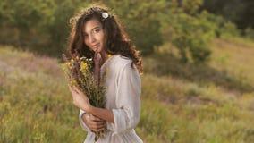 Naturlig skönhetflicka med buketten av blommor som är utomhus- i frihetsnjutningbegrepp Ståendefoto lager videofilmer