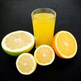 Naturlig smaklig fruktsaft som göras av citronen, apelsinen, mandarinen och raring på svart bakgrund Fruktbegrepp Royaltyfri Bild