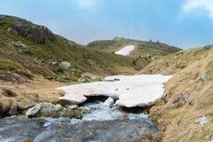 Naturlig snöbro som korsar en skattskyldig flod arkivfoto