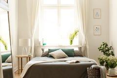 Naturlig sovruminre med en säng som omges av grupper av lösa blommor Stort soligt fönster i bakgrunden Verkligt foto arkivfoton