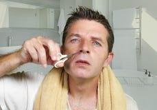 Naturlig stående för livsstil av den unga attraktiva och koncentrerade mannen som försiktigt klipper hår i hans näsa med liten sa arkivbilder