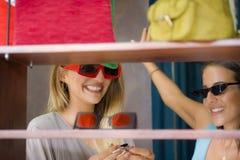 Naturlig stående för livsstil av unga härliga och lyckliga flickvänner som försöker på att shoppa för solglasögon som är gladlynt royaltyfria foton