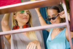 Naturlig stående för livsstil av unga härliga och lyckliga flickvänner som försöker på att shoppa för solglasögon som är gladlynt arkivbild