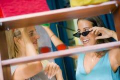 Naturlig stående för livsstil av unga härliga och lyckliga flickvänner som försöker på att shoppa för solglasögon som är gladlynt royaltyfri fotografi