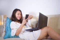 Naturlig stående för livsstil av ungt hemmastatt arbete för nätt och lycklig asiatisk koreansk studentkvinna på bärbar datordator royaltyfri bild