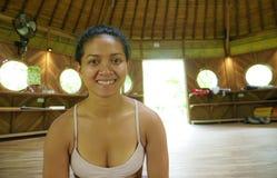 Naturlig st?ende av den unga attraktiva och lyckliga asiatiska indonesiska akrobatkvinnan som deltar i p? yogaworkoshop i traditi royaltyfria foton